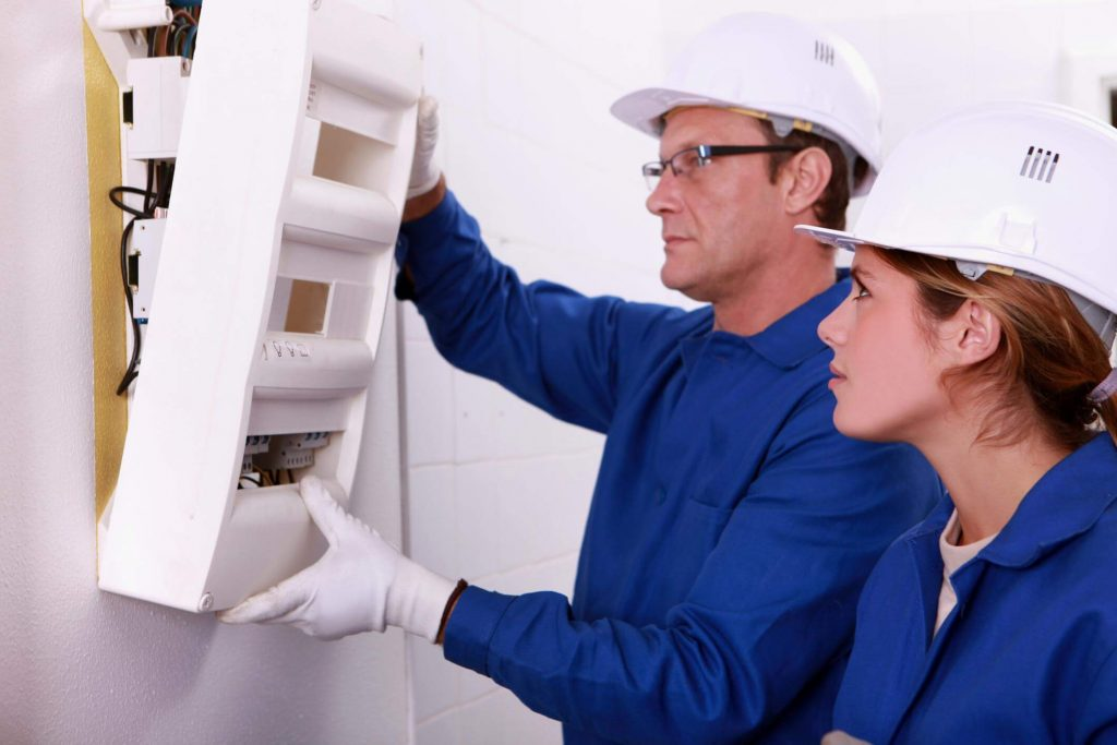 Younger female electrician assisting a senior male electrician in the removal of an electrical panel cover