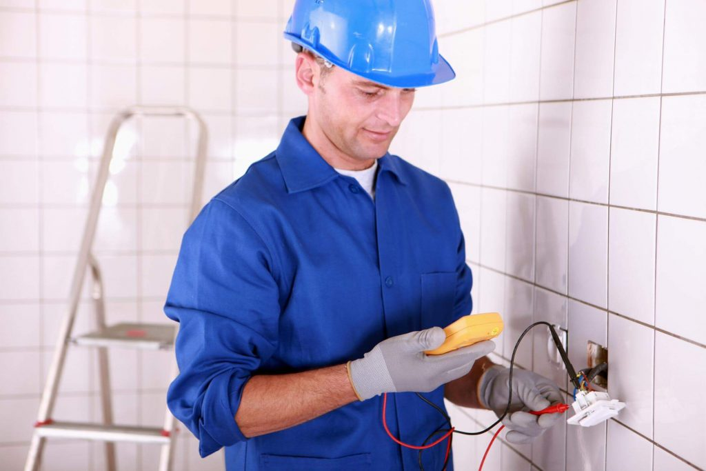 Male electrician checking a power socket with a power meter before attaching it to the wall