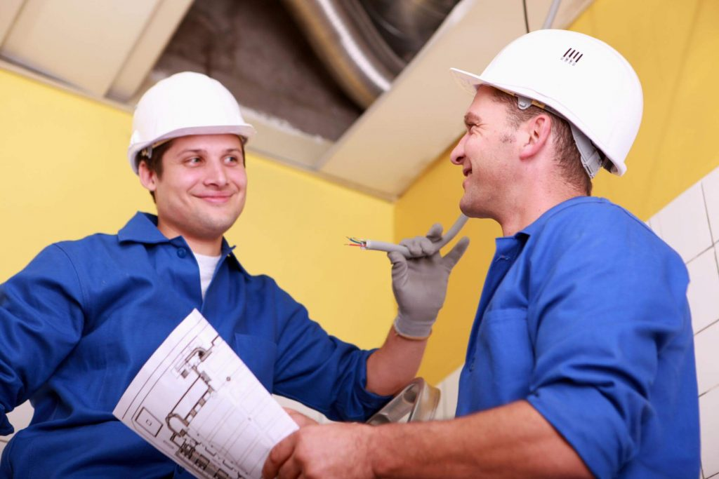 Two electricians smiling whilst discussing the job at hand. One of them is on a ladder holding a wire, the other is holding the electrical plan on paper