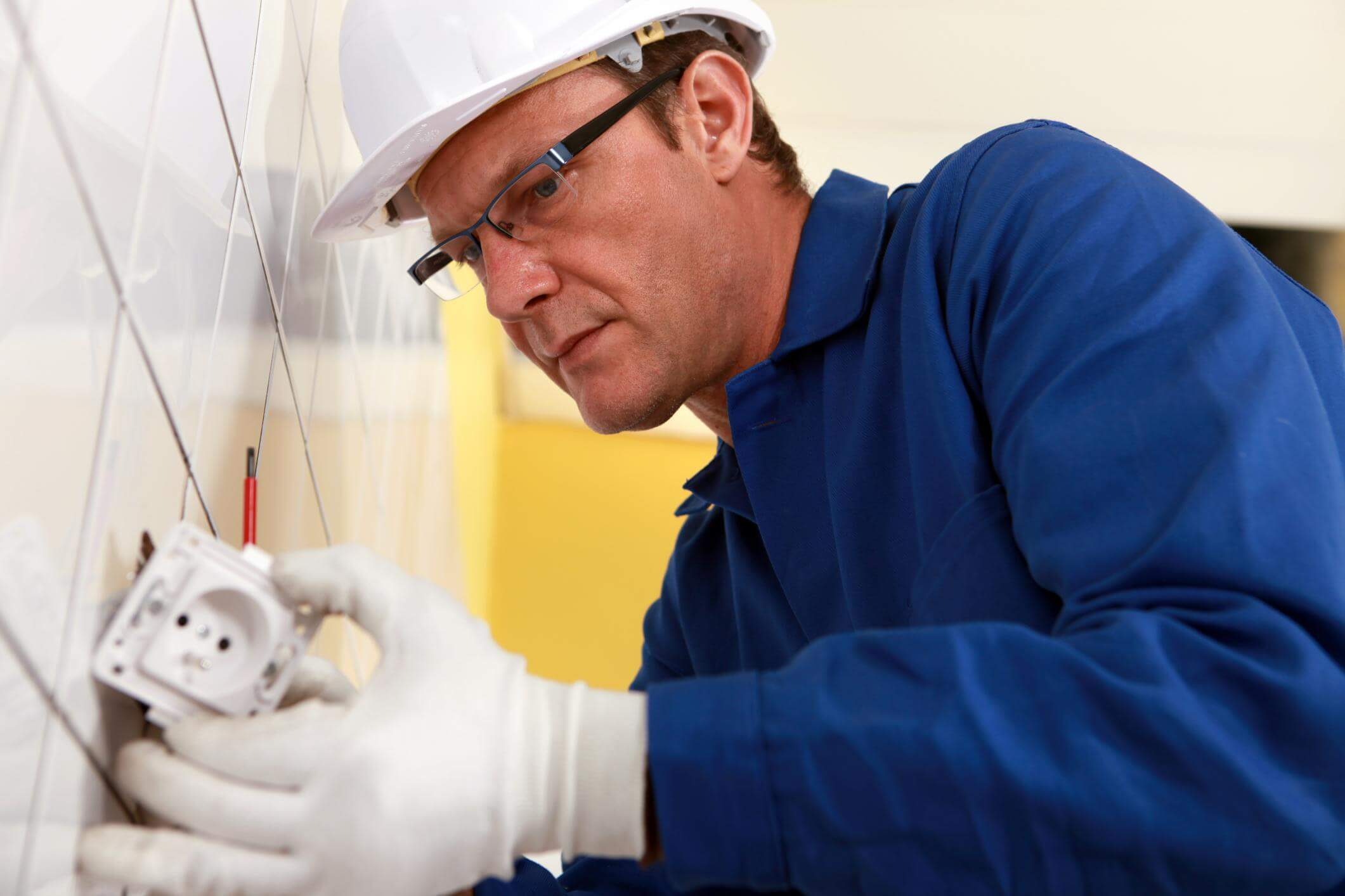 Senior electrician with glasses diligently installing a power socket