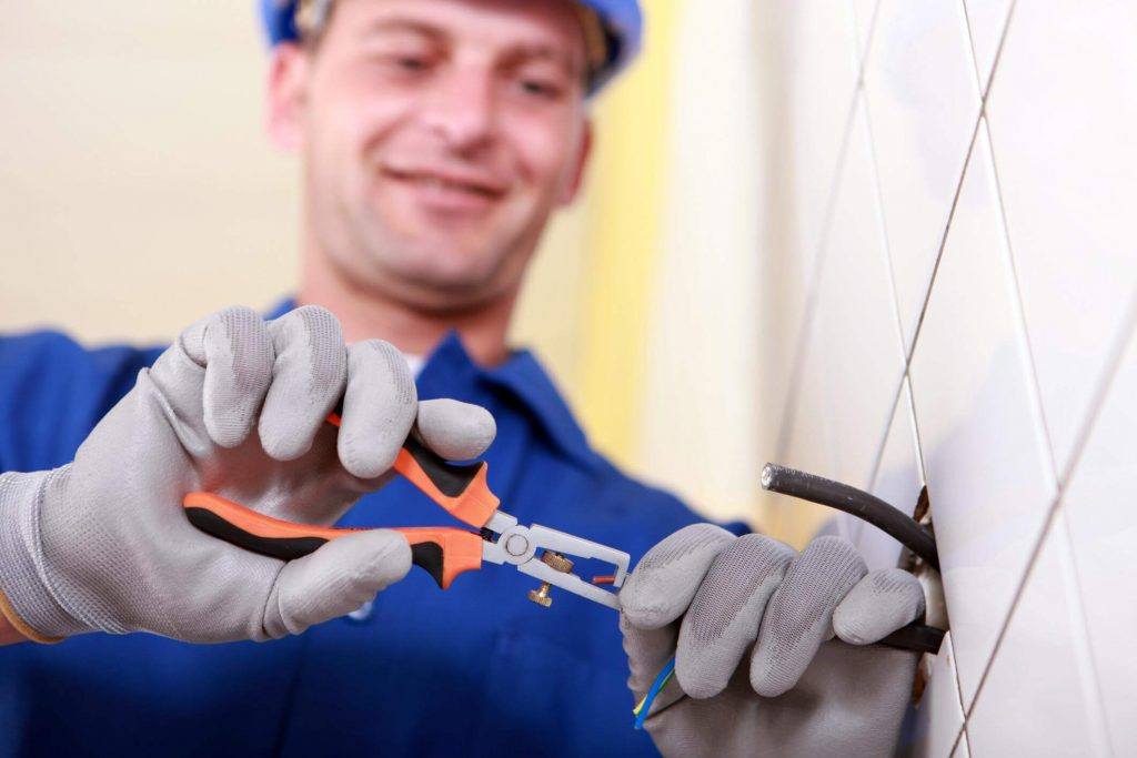 Male electrician smiling whilst using a wire cutter to cut a wire sticking out of a tiled wall