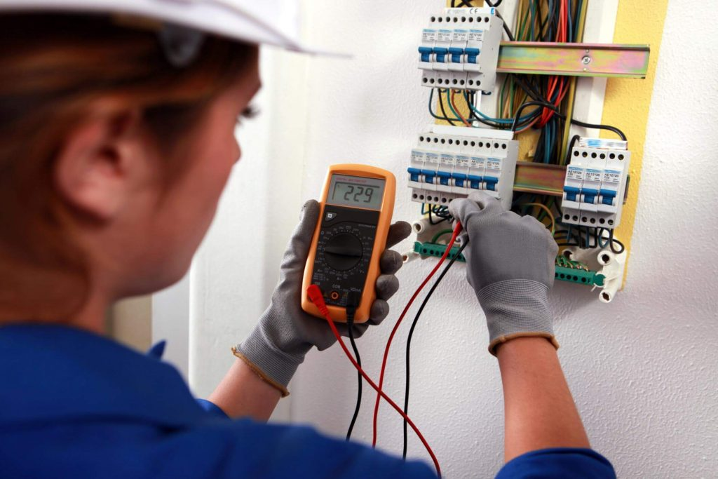 Female electrician with grey gloves and blue coveralls checking a residential main power breaker