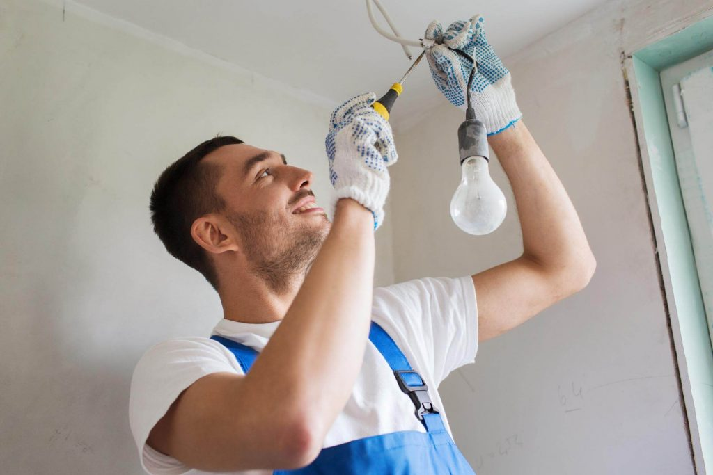 Male electrician with a trimmed beard installing lighting during a renovation
