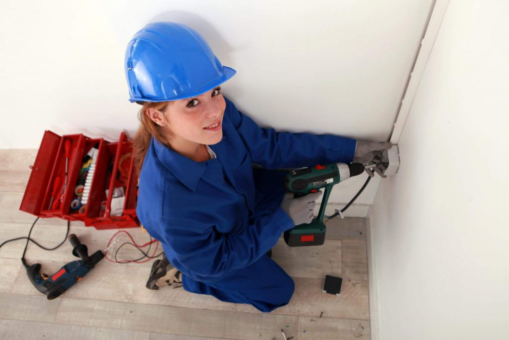 Smiling young female electrician in blue coveralls and a blue helmet using an electrical screwdriver to install an electrical wall socket, with behind her a red toolbox with several tools